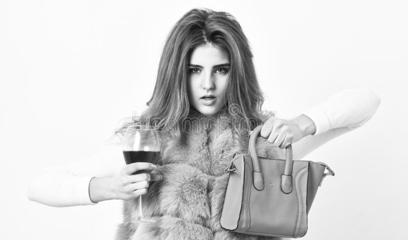 Woman with handbag hold glass of wine. Girl wear fashion fur vest while posing with bag. Luxury store concept. Elite. Fashion clothes. Lady likes shopping stock photo