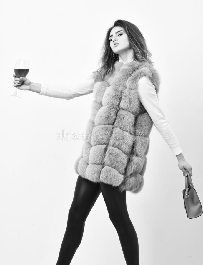 Woman with handbag hold glass of wine. Girl wear fashion fur vest while posing with bag. Luxury store concept. Lady. Likes shopping. Elite fashion clothes royalty free stock photos