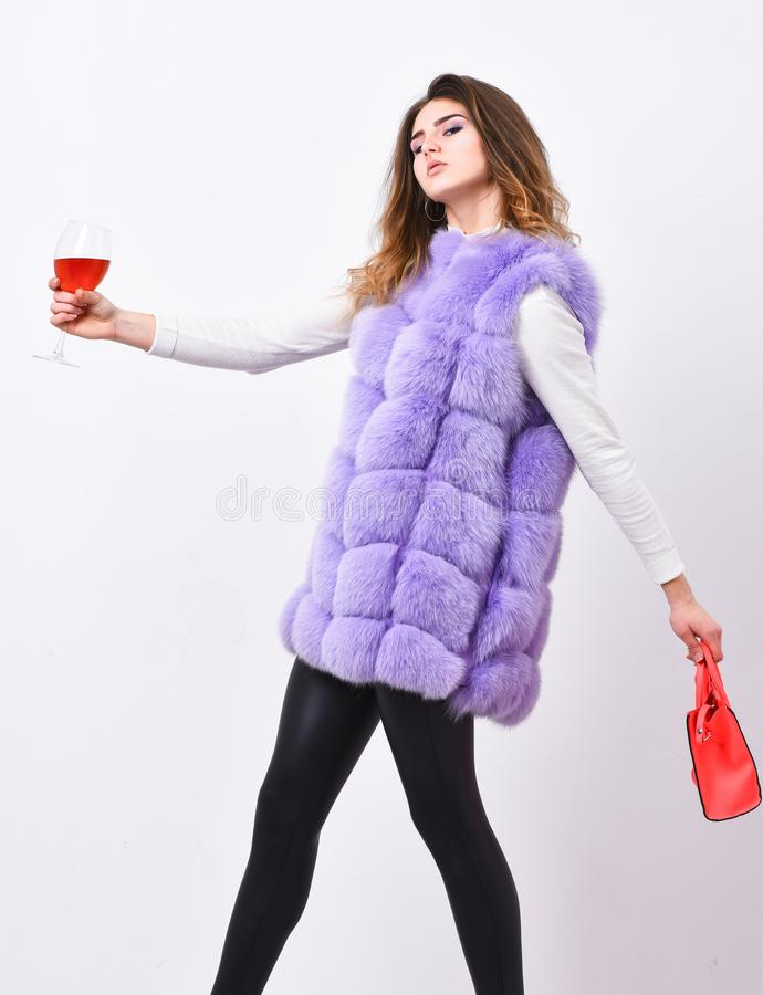 Woman with handbag hold glass of wine. Girl wear fashion fur vest while posing with bag. Luxury store concept. Lady. Likes shopping. Elite fashion clothes royalty free stock photo