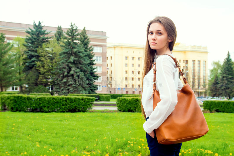 Woman with handbag. Outdoor portrait of young beautiful happy sensual woman with handbag, casual style, walking in city park royalty free stock photography