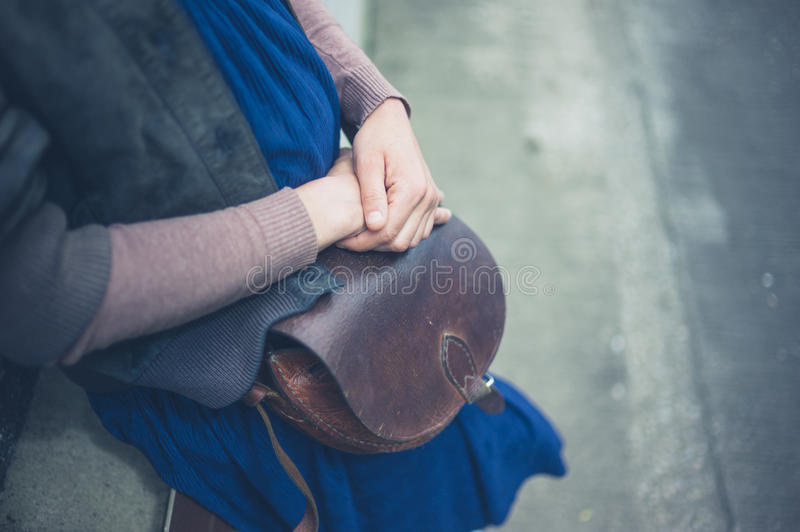 Woman with handbag outside. A young woman with a handbag outside in the city stock image