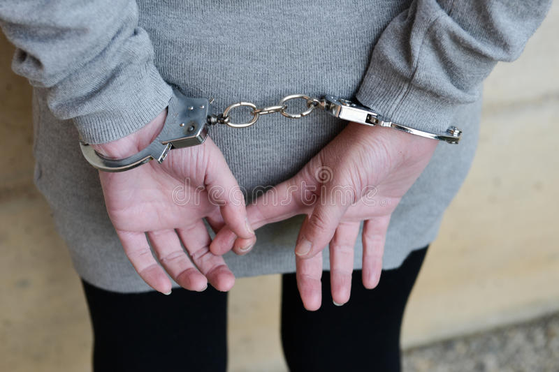 Woman in handcuffs behind her back stock image