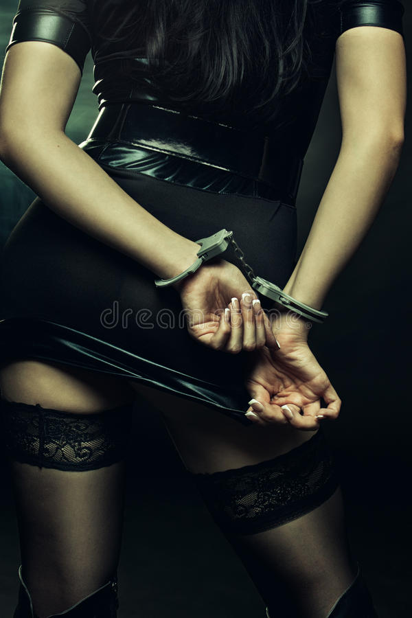 Woman in handcuffs. Seductive woman in handcuffs posing over dark background stock images