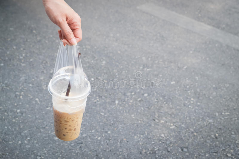 Woman handing a cup of cool coffee with blurred the road. royalty free stock photos