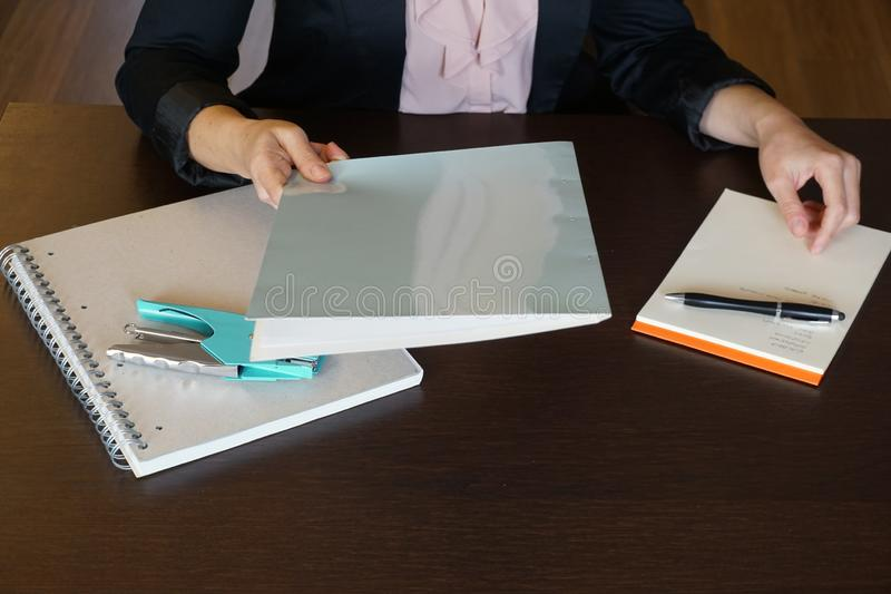 Woman is handing over a white file in direction camera while sitting at the desk in the office. stock photos