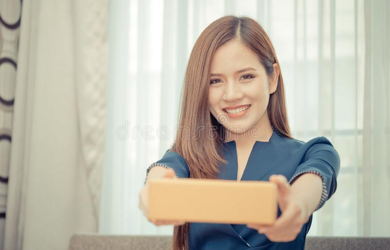 Woman handing package box from online shopping. Woman is handing package box from online shopping royalty free stock image