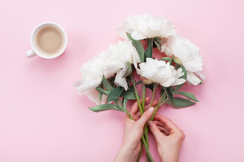 Woman hands with beautiful white peony flowers and cup of coffee on pink pastel table top view. Breakfast in flat lay style royalty free stock photo