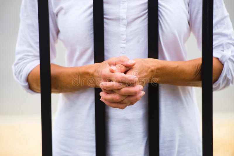 Woman with hands behind bars in prison. Close up Woman with hands behind metal bars in prison cell or cage, blurred background and copy space stock photography
