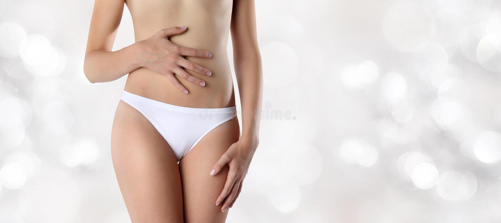 Woman hands on belly, on blurred lights background royalty free stock images