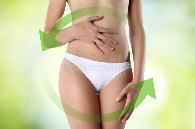 Woman hands on belly with green arrow. With white pant royalty free stock images