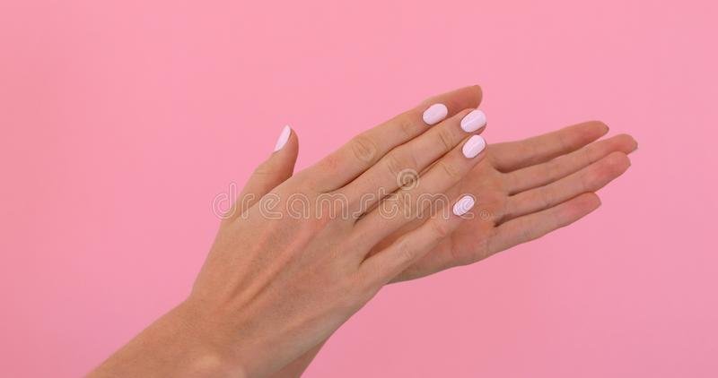 Woman hands clapping applause. Isolated over pastel pink background in studio royalty free stock photography