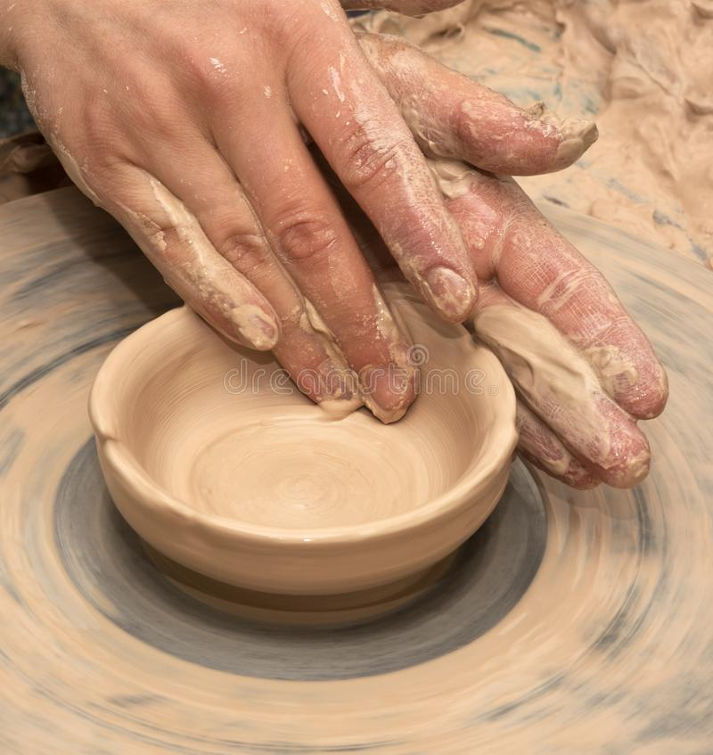 Woman hands in clay at process of making clay bowl on pottery wheel royalty free stock photos