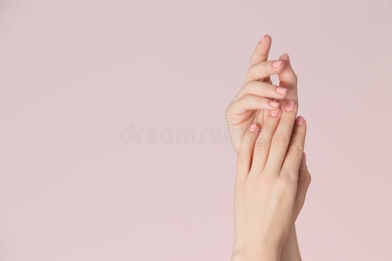 Woman hands with clean skin and nails with pink polish manicure on pink background. Nails care and beauty theme. Beauty background with copy space royalty free stock photo