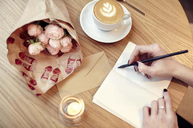 Woman hands close-up writing at notebook or postcard, blank layout for design. Flowers and coffee in cafe on wooden table, St. Val stock image