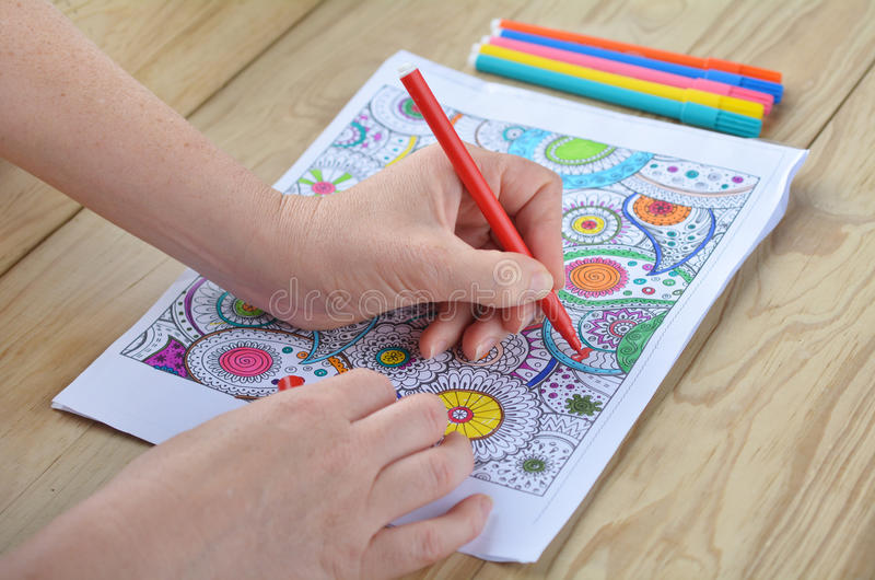 Woman hands coloring patterns on a coloring page for stress rel royalty free stock images