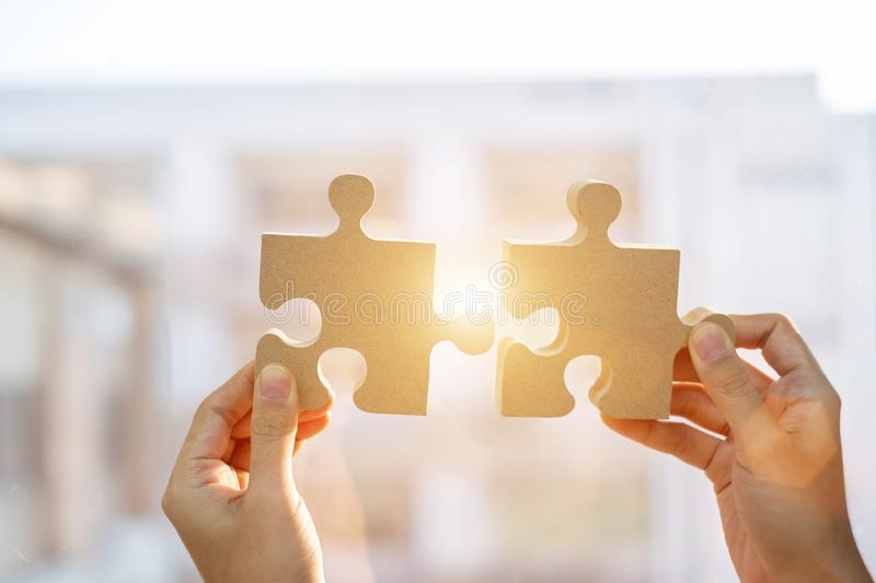 Woman hands connecting couple puzzle piece against sunrise effect, businesswoman holding wood jigsaw with sunset background. Business solutions, target stock photography