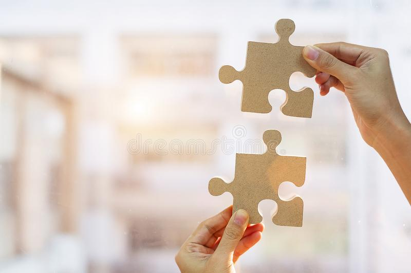 Woman hands connecting couple puzzle piece against sunrise effect, businesswoman holding wood jigsaw with sunset background. Business solutions, target royalty free stock image