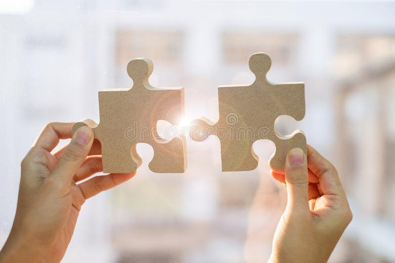 Woman hands connecting couple puzzle piece against sunrise effect, businesswoman holding wood jigsaw with sunset background. Business solutions, target stock images
