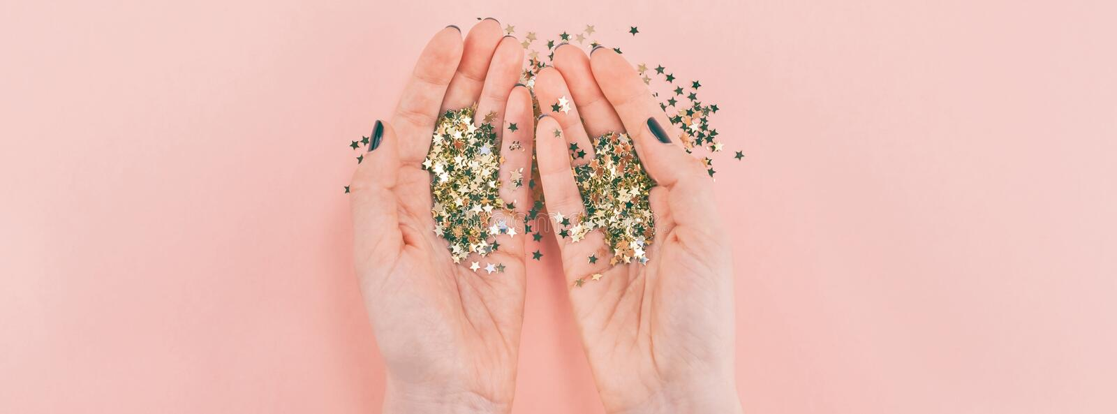 Woman hands covered golden stars confetti on pink royalty free stock image