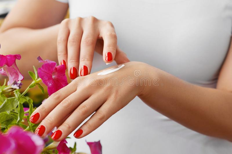 Woman Hands With Cream. Closeup Of Beautiful Female Hands With Red Manicure Nails Applying Cosmetic Lotion On Healthy Soft Skin, stock photos