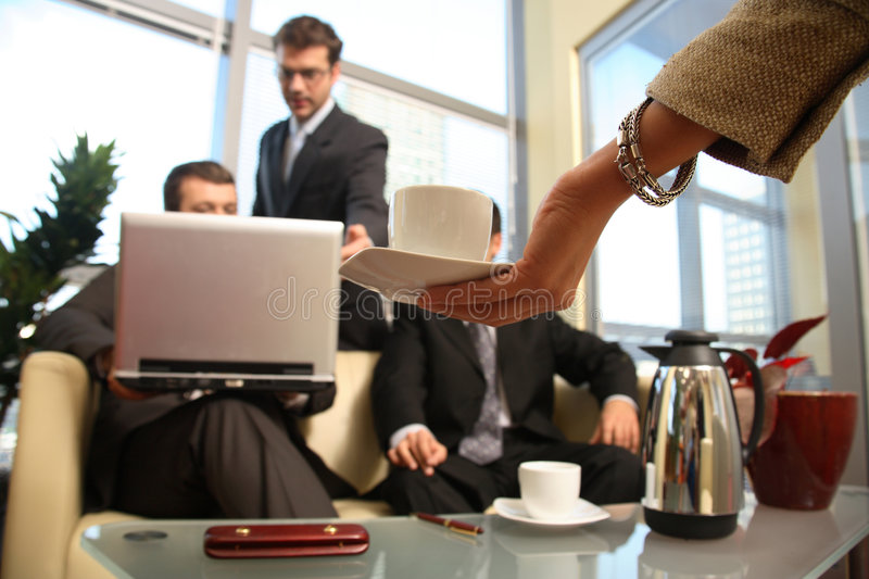 Woman hands cup to men in meeting stock photo