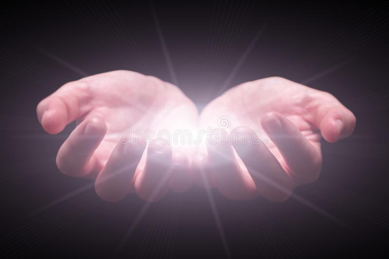 Woman hands cupped protecting and holding bright, glowing, radiant, shining light. Emitting rays or beams expanding. Religion, divine, heavenly, celestial royalty free stock photo