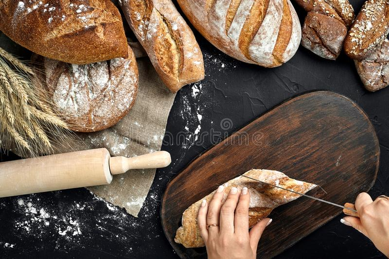 Woman hands cutting a loaf of bread on rustic wooden board, with wheat ears and knife, top view. royalty free stock photography
