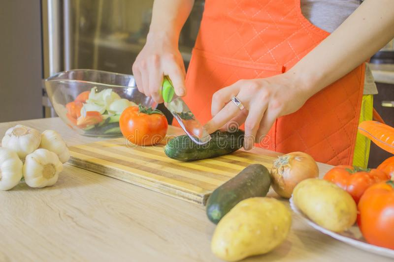 Woman hands cutting vegetables on kitchen blackboard. Healthy food. Woman preparing vegetables, cooking healthy meal in the royalty free stock photos