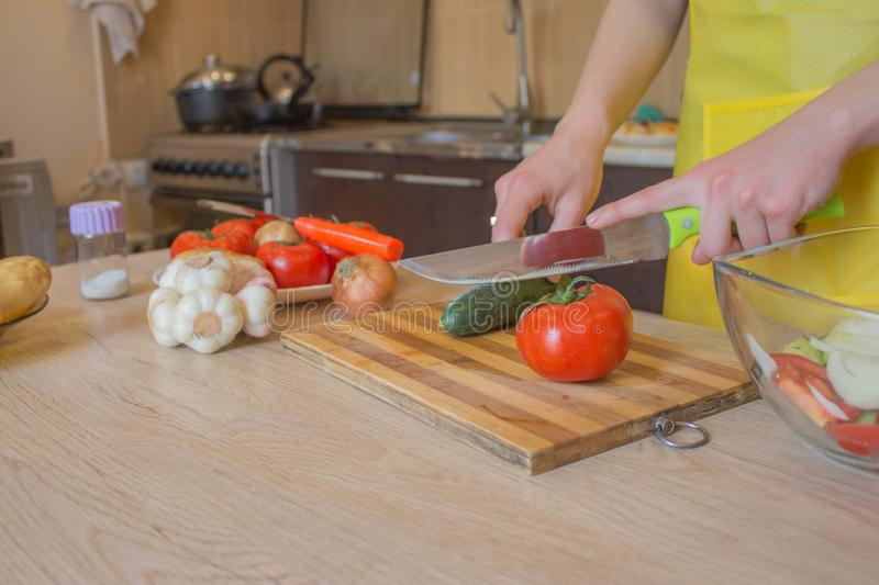 Woman hands cutting vegetables on kitchen blackboard. Healthy food. Woman preparing vegetables stock images
