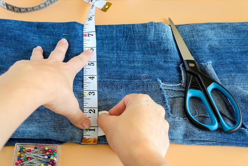 Woman hands drawing a cut line on jeans before cutting. Blue jeans with a large hole on a leg folded in half and pinned with pins. Woman hands drawing a cut line royalty free stock photography