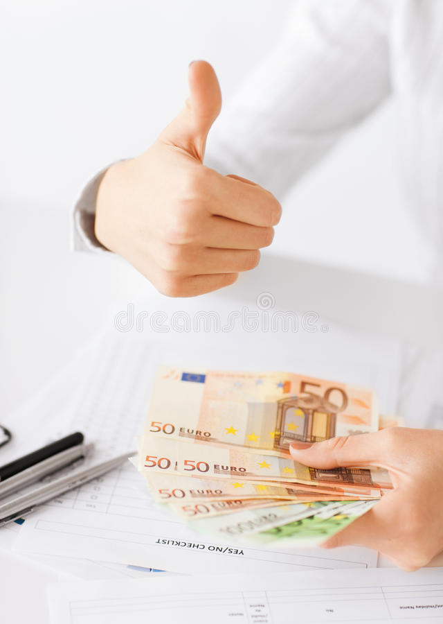 Woman hands with euro cash money and thumbs up royalty free stock photography
