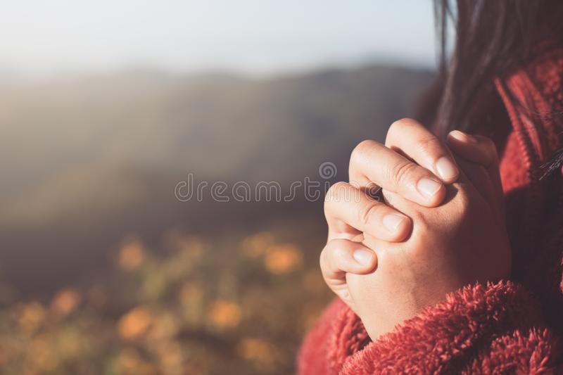 Woman hands folded in prayer in beautiful nature background royalty free stock photography