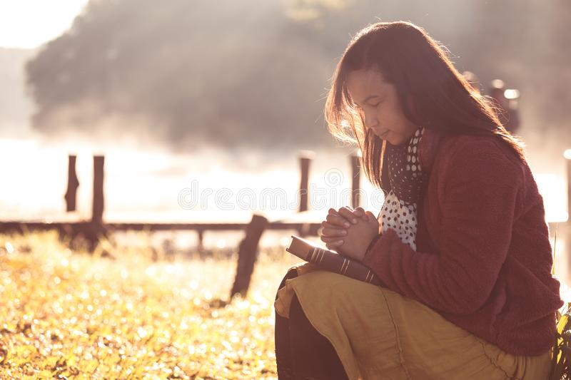 Woman hands folded in prayer on a Holy Bible for faith stock photo