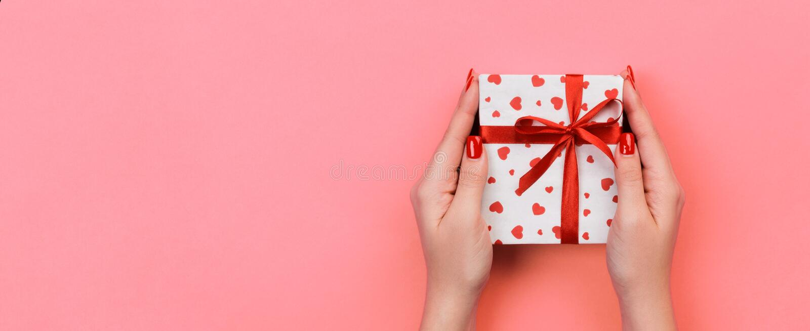 Woman hands give valentine or other holiday handmade present in paper with red ribbon. Present box, red heart decoration of gift. On Coral color table, Top view stock photography