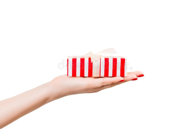 Woman hands give wrapped Christmas or other holiday handmade present in red paper with gold ribbon. Isolated on white background, royalty free stock images