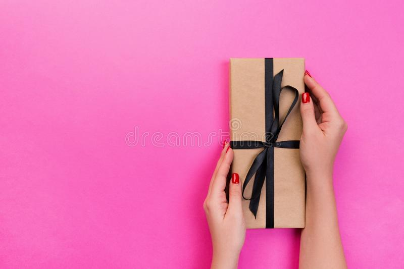 Woman hands give wrapped valentine or other holiday handmade present in paper with black ribbon. Present box, decoration of gift stock photos