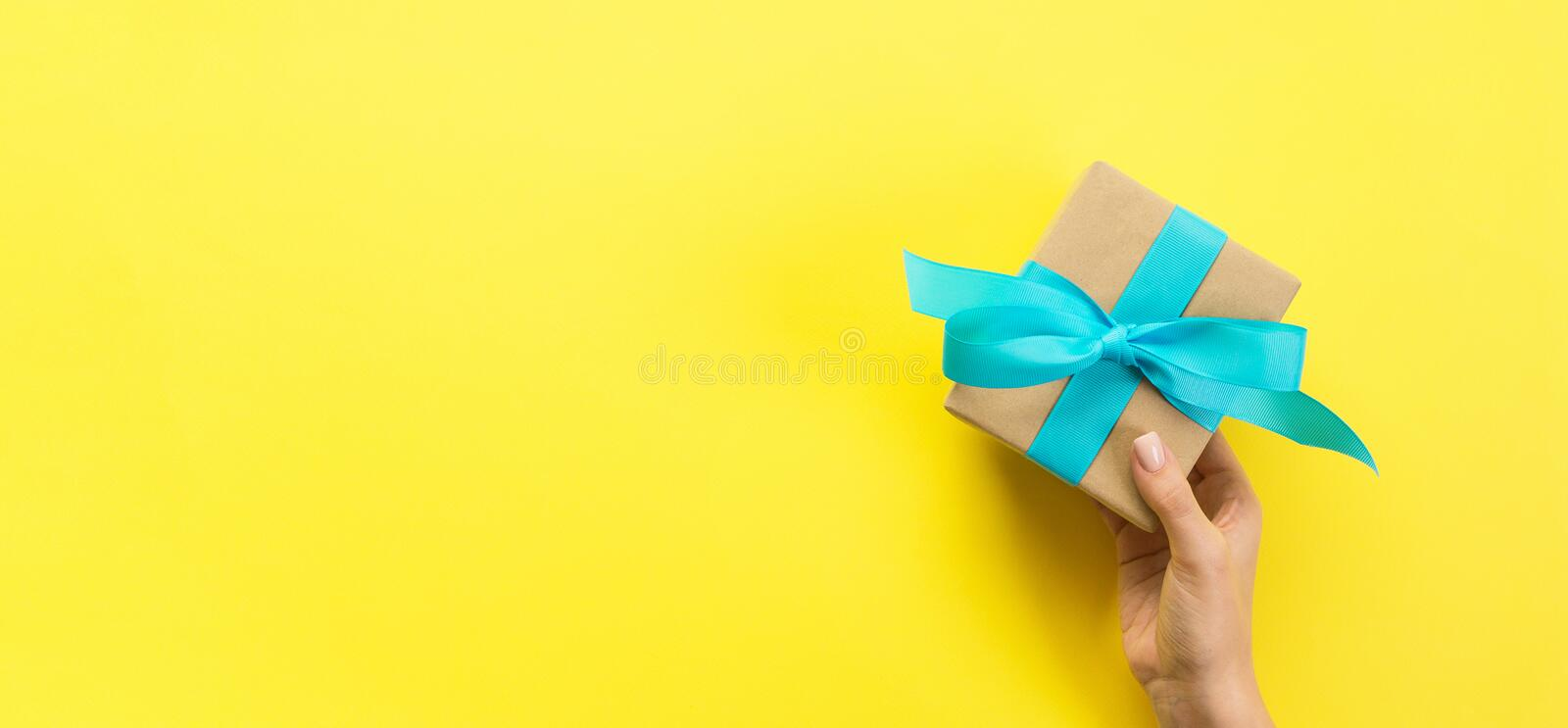 Woman hands give wrapped valentine or other holiday handmade present in paper with blue ribbon. Present box, decoration of gift on. Yellow table, Top view stock image