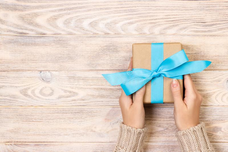 Woman hands give wrapped valentine or other holiday handmade present in paper with blue ribbon. Present box, decoration of gift on stock images