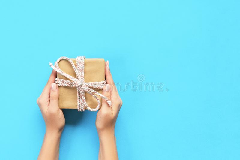 Woman hands give wrapped valentine or other holiday handmade present in paper with blue ribbon. Present box, decoration of gift on. Table, top view with copy stock images