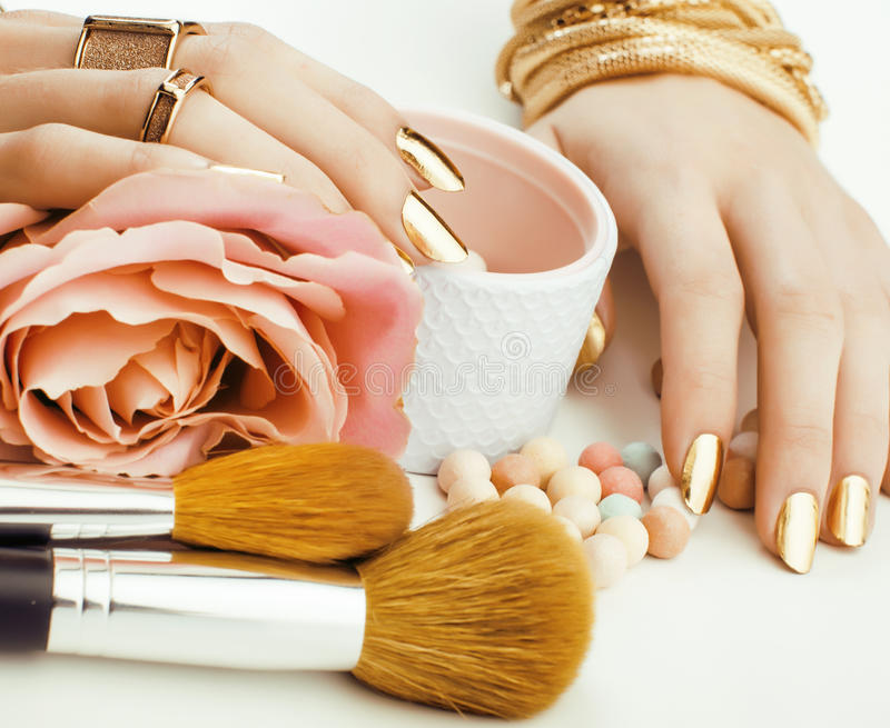 Woman hands with golden manicure and many rings holding brushes, makeup artist stuff stylish, pure close up pink. Beauty concept stock image