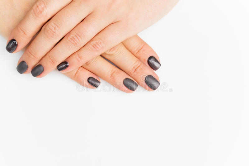Woman hands with grey nails. Manicure. Over white background. Copy space stock photos
