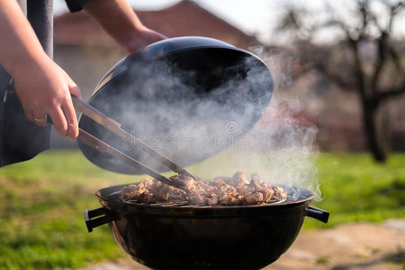 Woman hands grilling barbecue meet on the grill outdoors in the back yard. Summer time picnic. Roasting meat on metal grid on hot royalty free stock photography