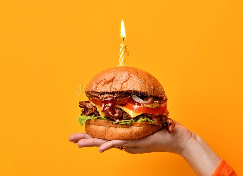 Woman hands hold big burger barbeque sandwich with beef and lit candle for birthday party on yellow. Background royalty free stock images