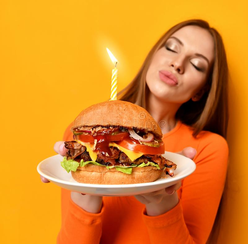 Woman hands hold big burger barbeque sandwich with beef and lit candle for birthday party on yellow. Woman hold big burger barbeque sandwich with beef and lit stock images