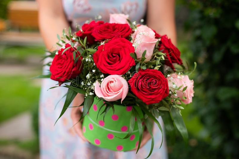 Woman hands hold box with flower bouquet of red and pink roses o stock photo
