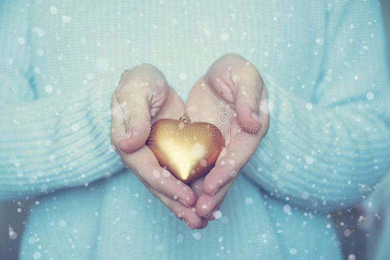 Woman hands are holding a beautiful glossy gold heart in a snow winter background. Love and St. Valentine cozy concept. stock photo