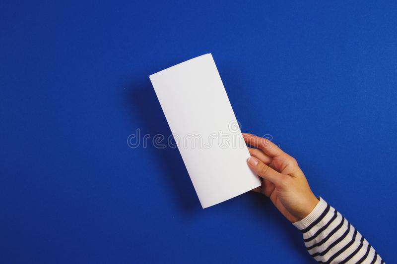 Woman hands holding blank white flyer brochure booklet. Mockup sheet template advertising booklet on blue background. Woman hands holding blank white flyer royalty free stock image