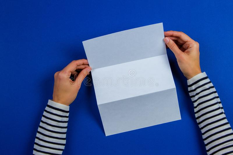 Woman hands holding blank white flyer brochure booklet. Mockup sheet template advertising booklet on blue background. Woman hands holding blank white flyer royalty free stock photography
