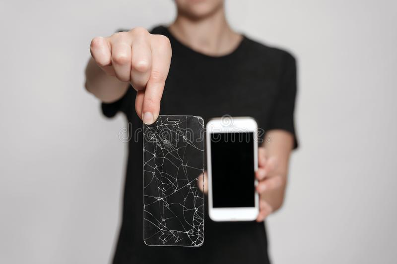 Woman hands holding broken screen protection and saved smartphone. Phone save concept. Isolated on gray background. Free copy space for your advertise stock photography