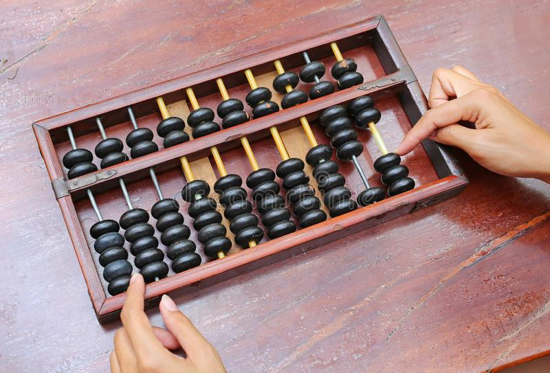 Woman hands holding Chinese ABACUS old antique calculator retro finance education, tool work business accounting royalty free stock photo